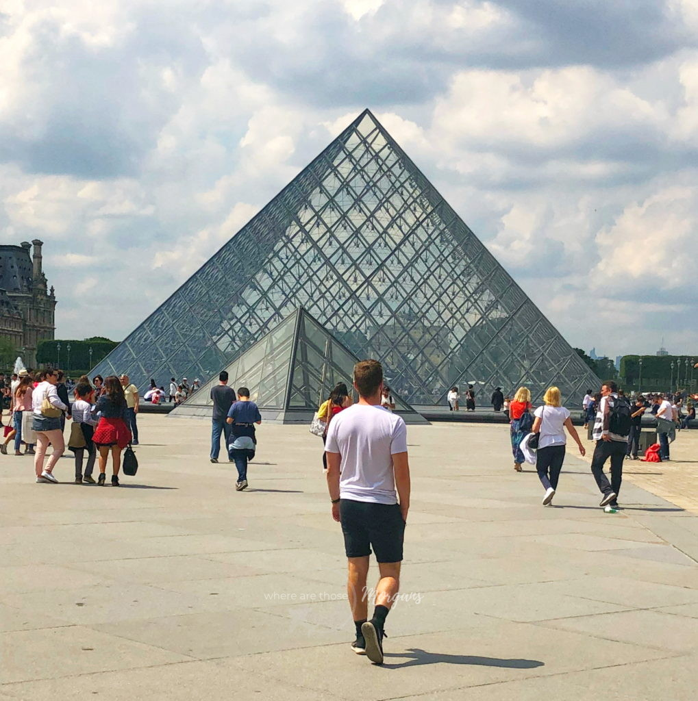Mark walking in front of the Louvre