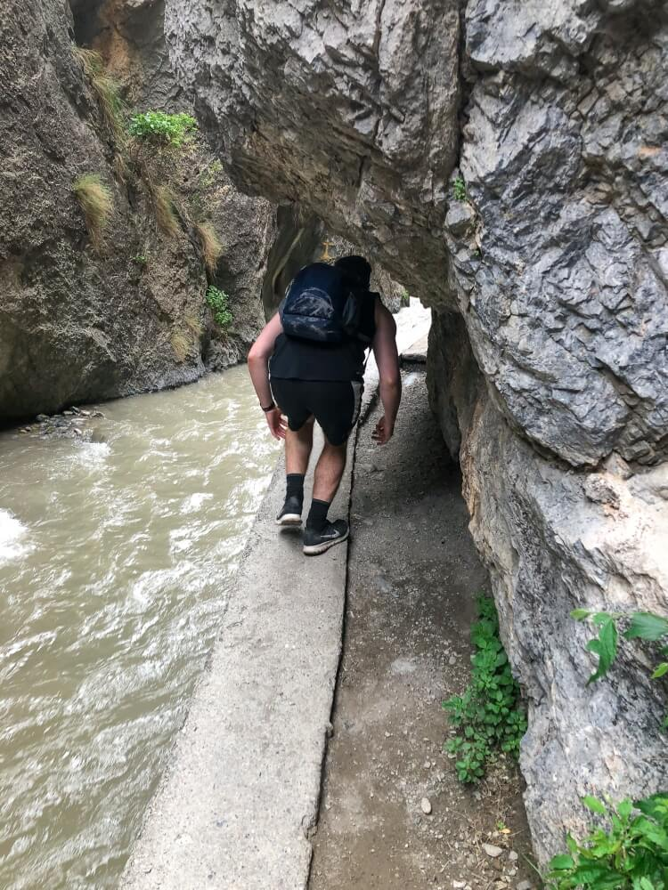 Mark needing to duck to get through hiking trail in Sierra Nevada