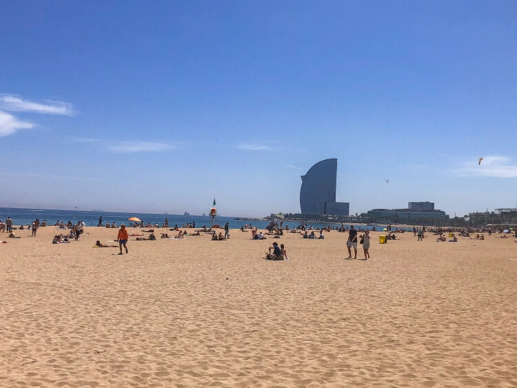 Many tourists enjoying the sun and sand on Barcelonata Beach