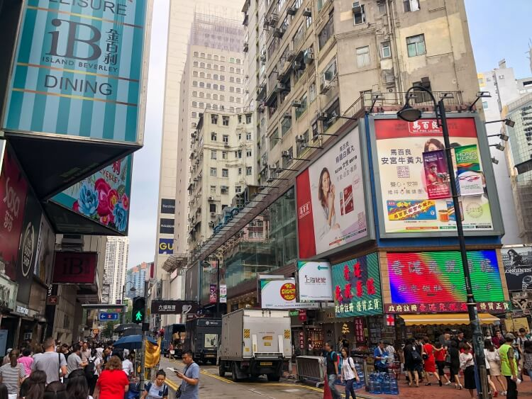 street signs and people walking in Causeway Bay