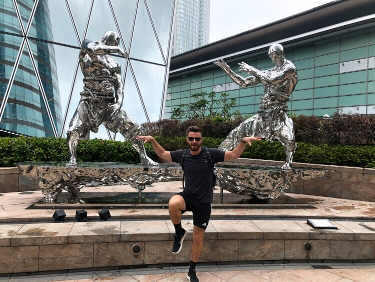 Mark posing with statues in Hong Kong