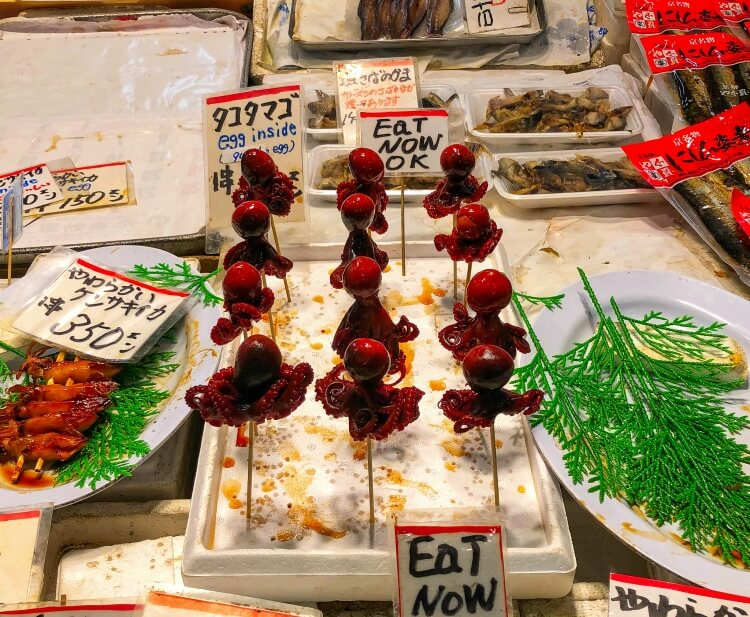 Market in Japan with baby octopus delicacy - travel food