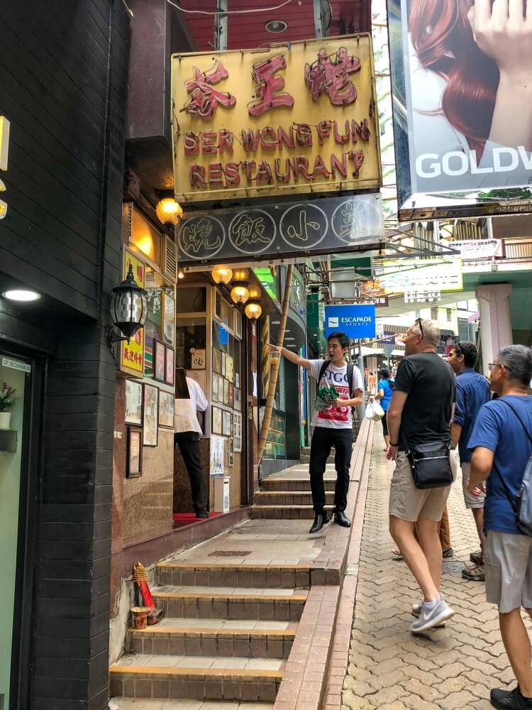 a guide pointing to a sign as something to do in Hong Kong