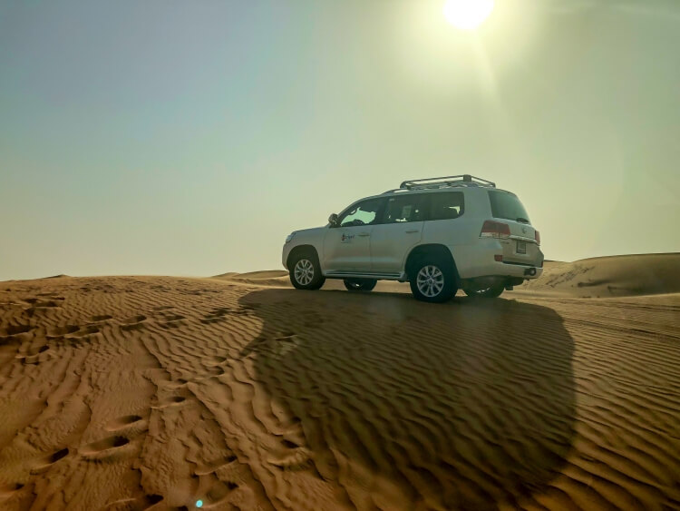 a 4x4 parked on a sand dune with the sun showing in the background