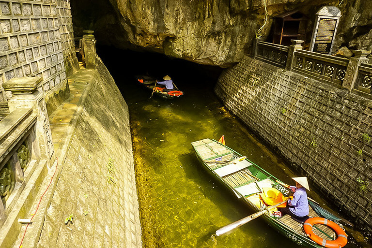 wooden boats going inside cave tunnel Ninh Binh