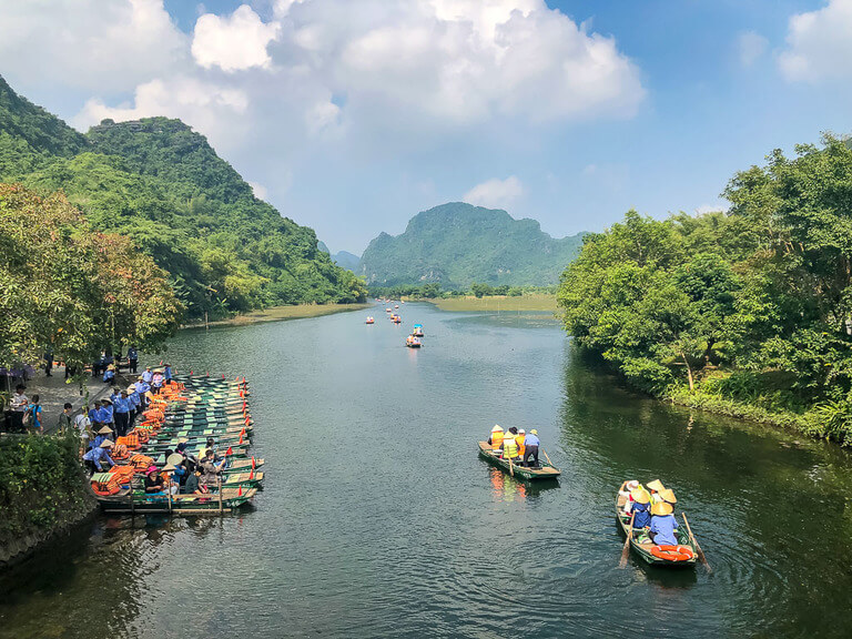 wooden boats leaving dock heading upriver
