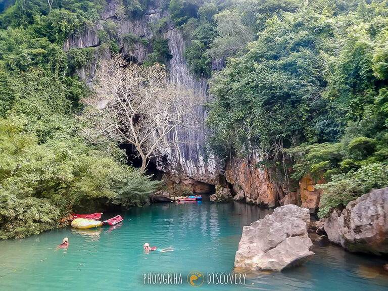 Swimming up to dark cave entrance in turquoise water
