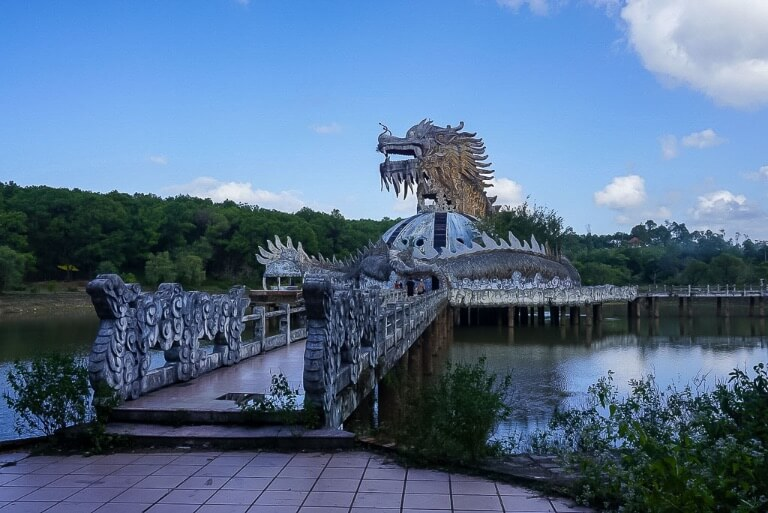 narrow bridge leading over lake to dragon building in hue