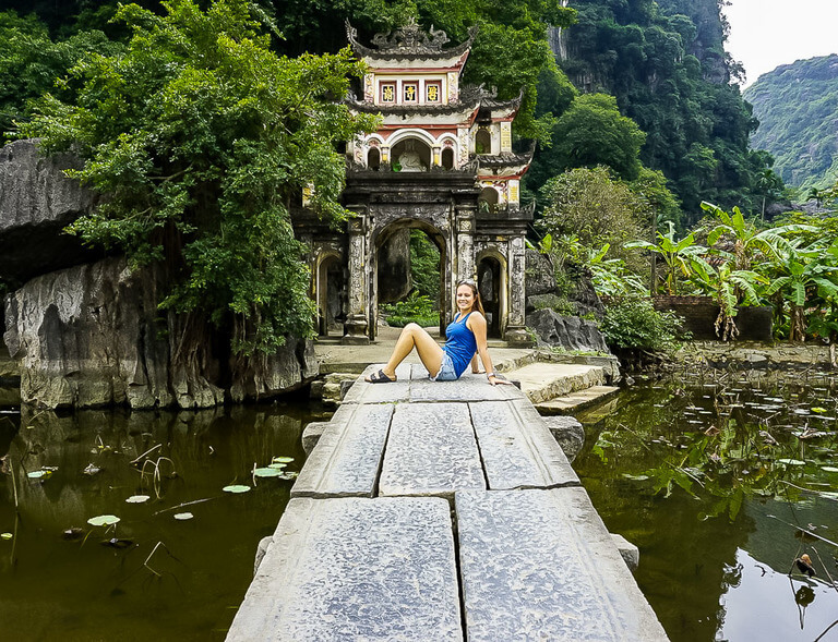 Kristen sat on narrow stone path leading to pagoda entrance Ninh Binh