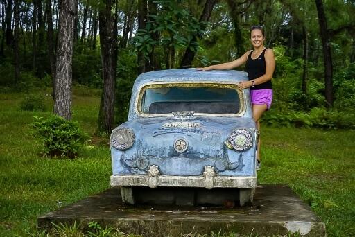 Kristen stood on side of little blue stone car