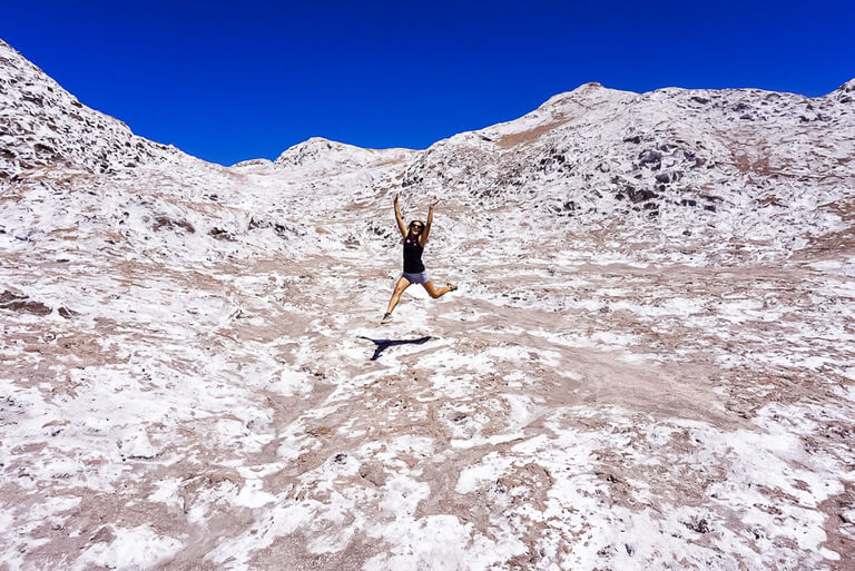 kristen leaping into the air above salty rocks in valley of the moon Atacama Desert