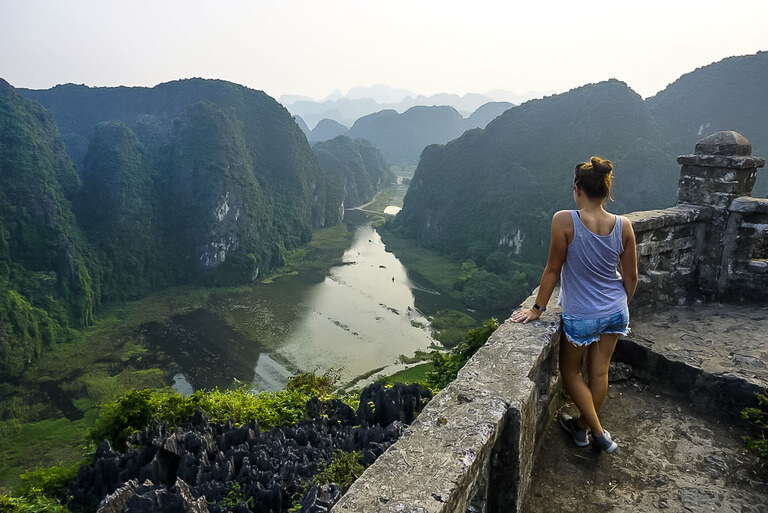 Kristen stood leaning against stone wall overlooking viewpoint on Ninh Binh itinerary