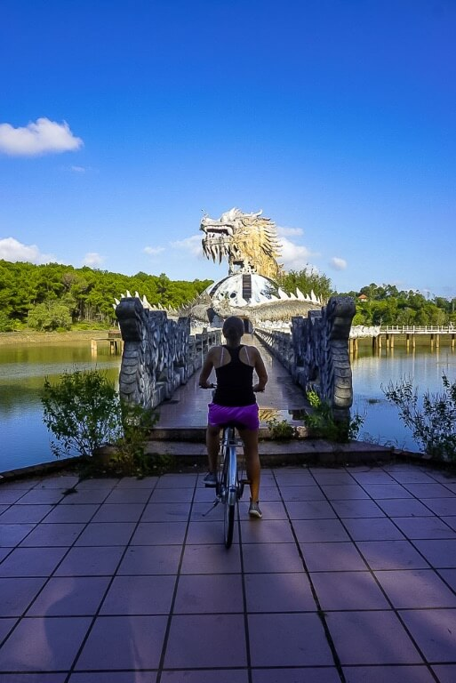 Kristen on bicycle in front of narrow bridge leading to abandoned dragon building hue water park