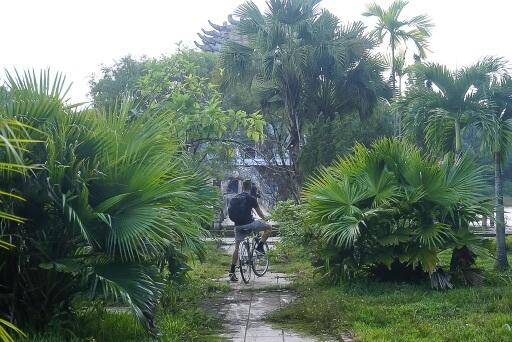 Mark on bike surrounded by green vegetation