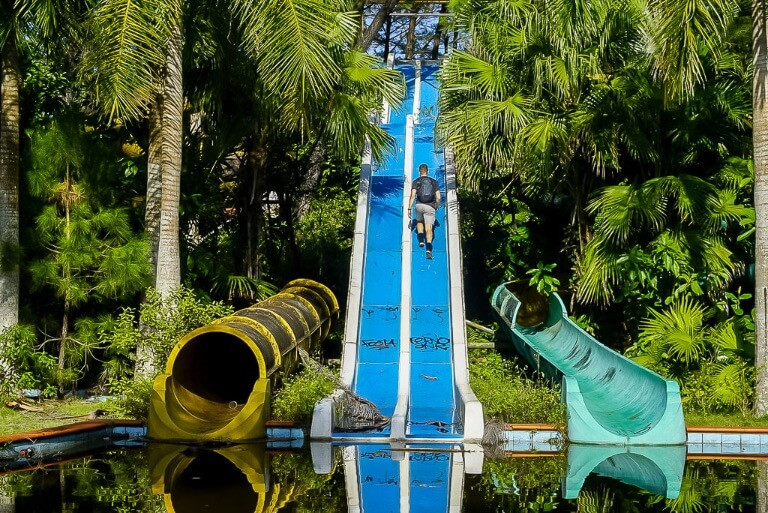 Mark walking up an abandoned blue water slide into trees