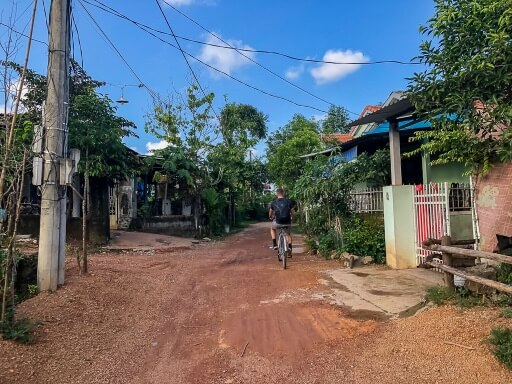 mark cycling along dirt road with group getting into abandoned water park hue