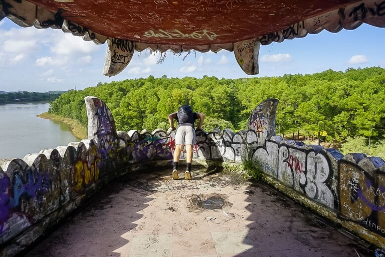 Mark looking at the drop out of a dragons mouth in hue abandoned water park