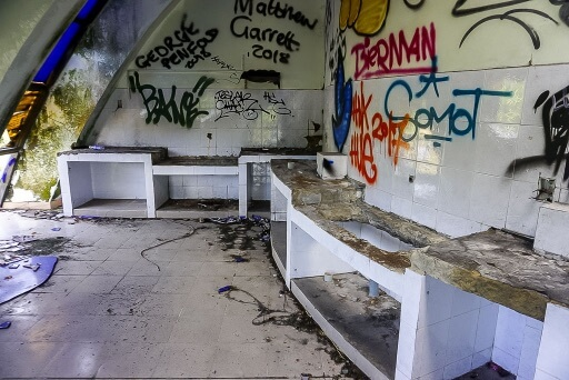 rundown room wit graffiti and smashed glass in hue