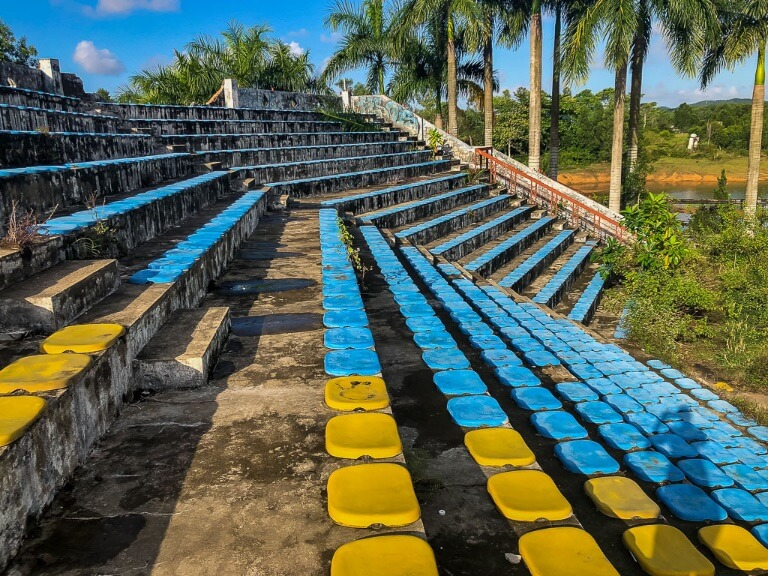 blue and yellow seats amphitheater in abandoned water park hue overgrown with vegetation