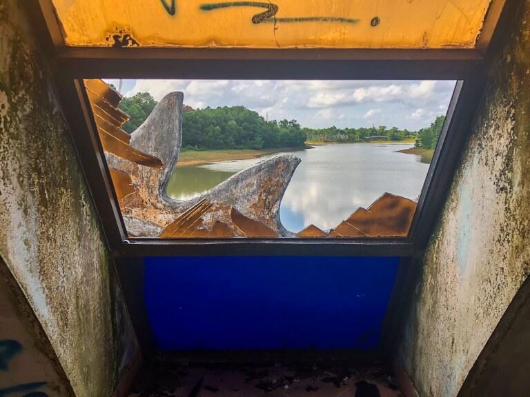 inside dragon at abandoned water park hue smashed window overlooking lake