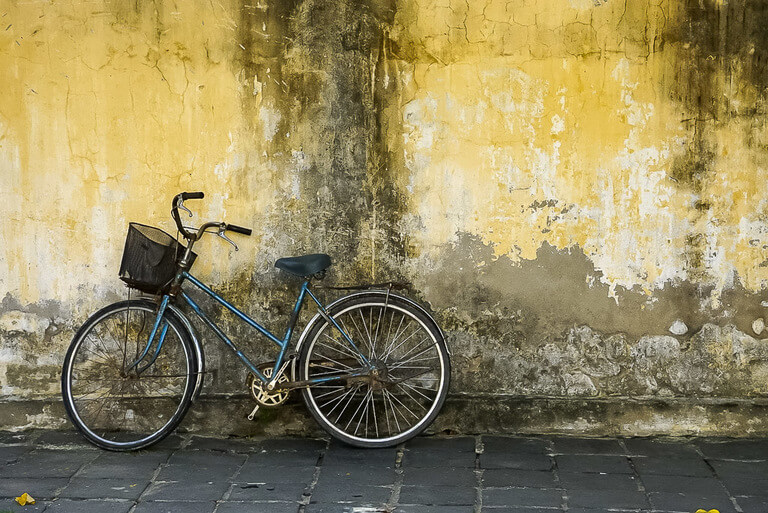 Bike leaning up against yellow wall in Hoi An vietnam