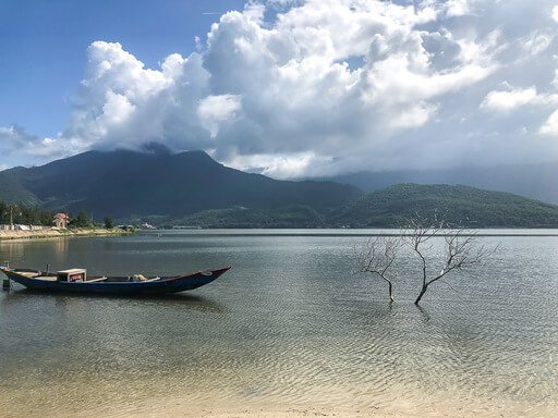 wooden boat and branches poking out of lake in Vietnam