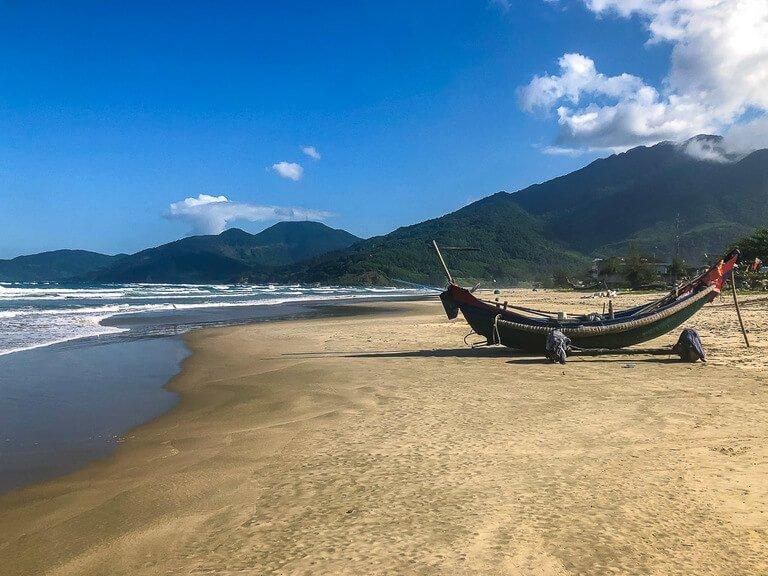 Banana shaped wooden boat on Lang Co beach between hue and Hoi An Vietnam