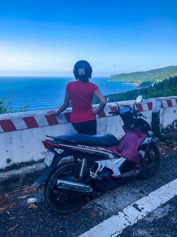 Kristen enjoying the view from Hai Van Pass with motorbike parked