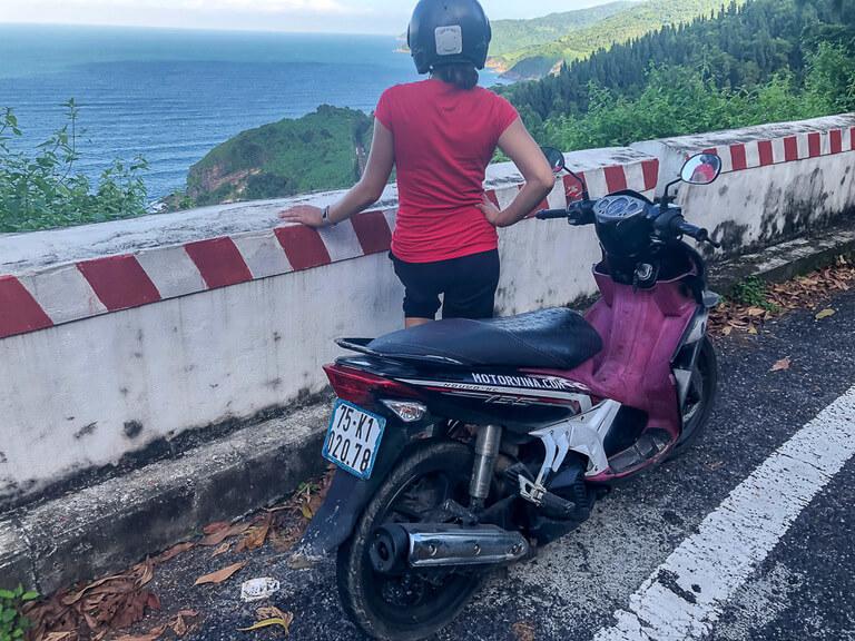 Kristen with motorbike and helmet on looking to sea on hai van pass vietnam
