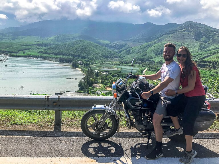 Mark and Kristen on Dr Phu motorbike with green hills and lake background