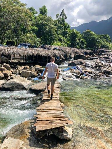 Mark walking over a wooden bridge over a river