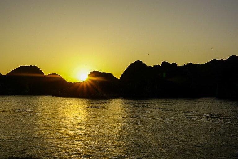 Sunset over limestone karsts Halong Bay