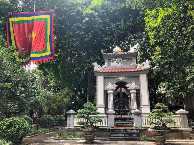 Small white temple and flag flying surrounded by trees