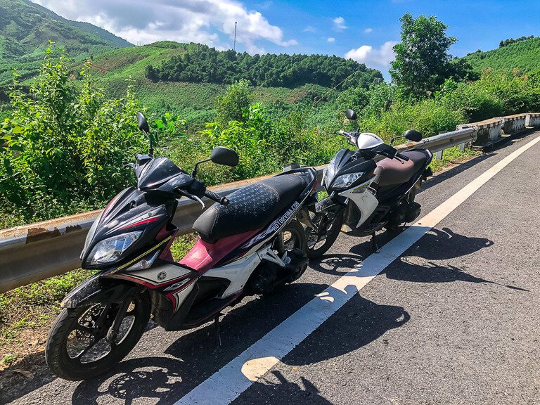 Mark and Kristens pink and white motorbikes on side of road crossing hai van pass Vietnam