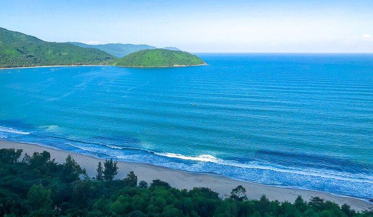 Da Nang Bay blue sea and beach with green trees