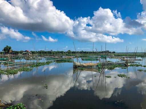 Wooden boats and fishing nets on lake in countryside between hue and Hoi An