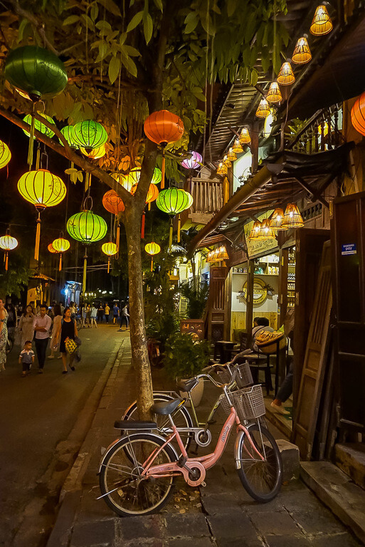 Hoi An old town at night lanterns and a bike propped against a tree vietnam