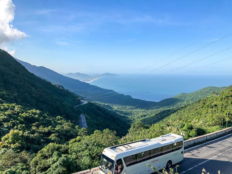 Coach driving up Hai Van pass between hue and da nang green trees and sea behind
