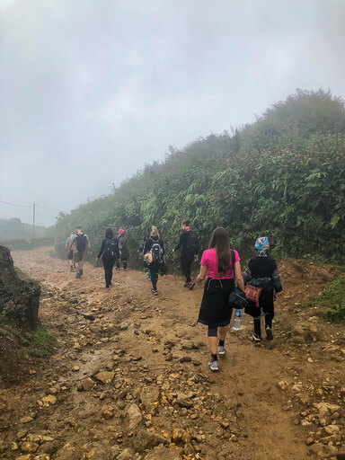 Kristen hiking along a dirt track in clouds sapa
