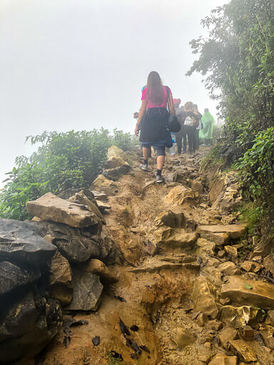 Kristen walking up rocky path in clouds sapa itinerary vietnam