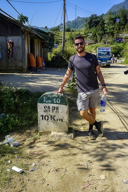 Mark leaning on sapa stone sign end of 2 days trekking vietnam