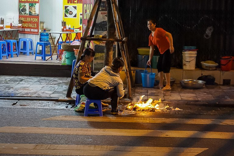 Food being cooked on a street with flames