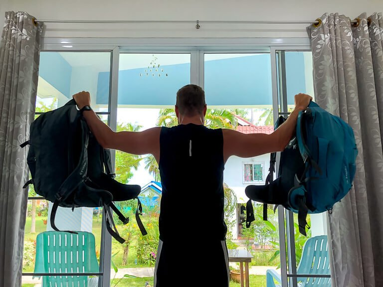 Mark doing shoulder raises with backpacks improvised workouts when traveling