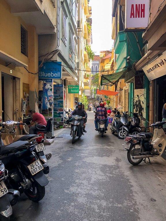2 motorbikes pass each other on narrow alleyway road in hanoi Vietnam