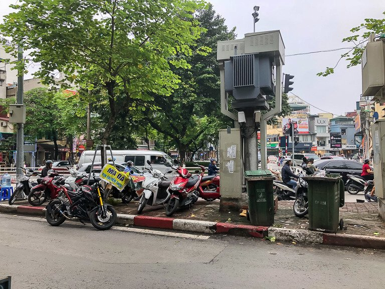 trash cans and motorbikes parked in between roads