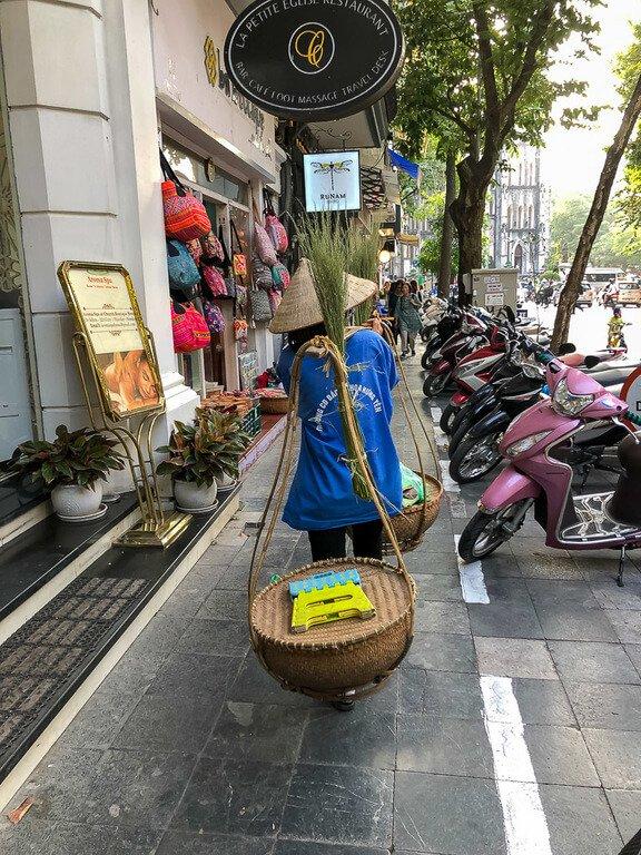 woman carrying fruit baskets on sidewalk in Vietnam