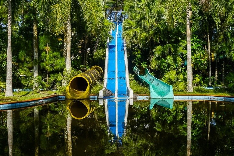 Water slides reflecting in water abandoned water park hue sixth stop on 3 week Vietnam Itinerary