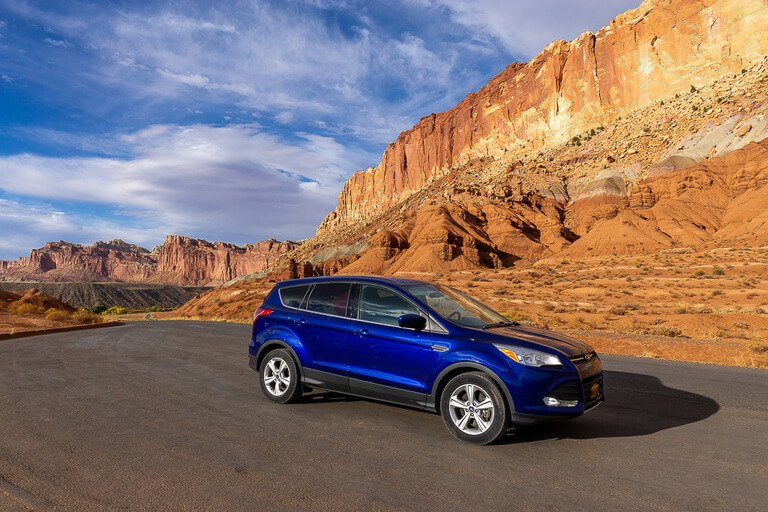 Big Blue parked on open road with huge towering rocks behind