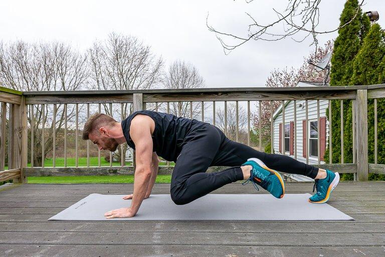 Mark doing mountain climbers on yoga mat