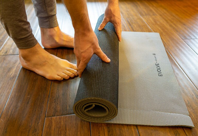 Mark unrolling a yoga mat on hard wood floor perfect traveling workouts